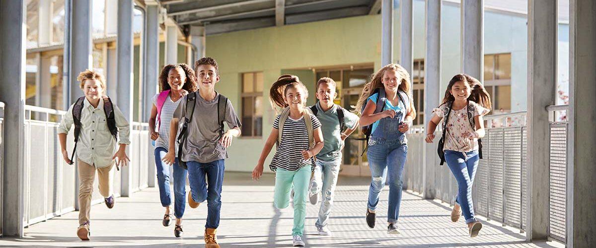 School kids running in elementary school corridor, close up